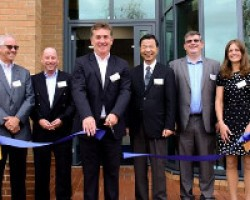 Photograph shows Jerry Davies (Managing Director, Roland DG (UK) Ltd) cutting the ribbon to mark the official opening of Roland DG UK's new head office and Creative Centre. Overseen by Mr Tomioka, President of Roland DG Corporation and members of the Roland DG senior management team, both in the UK and internationally
